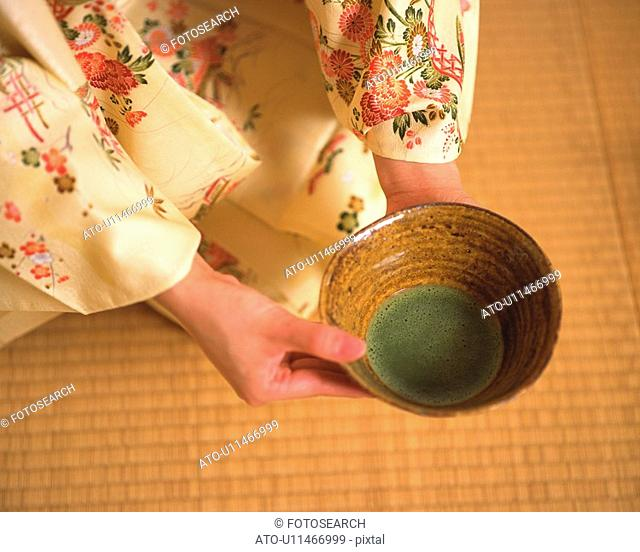 Woman in kimono holding a tea cup at tea ceremony, high angle view, Japan, differential focus