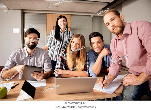 Work with pleasure. Positive blonde woman wearing checked shirt keeping smile on face while sitting between her friends