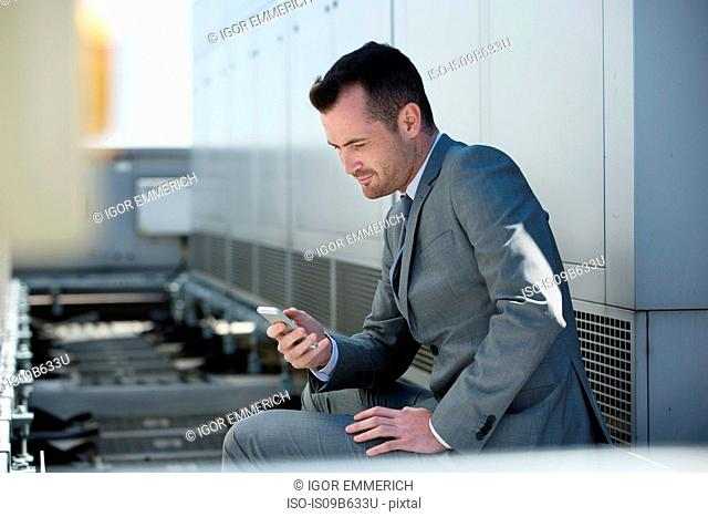 Businessman sitting outdoors, looking at smartphone