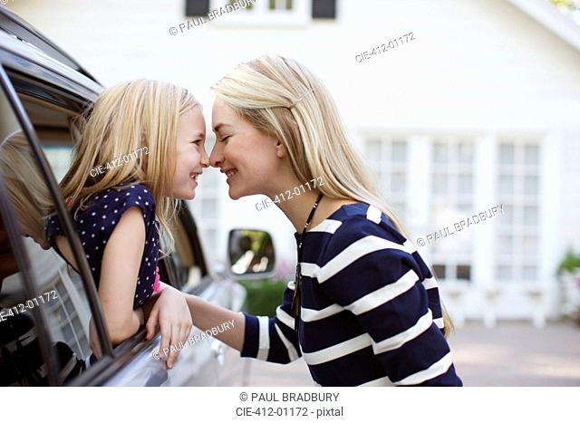 Mother and daughter touching noses in car