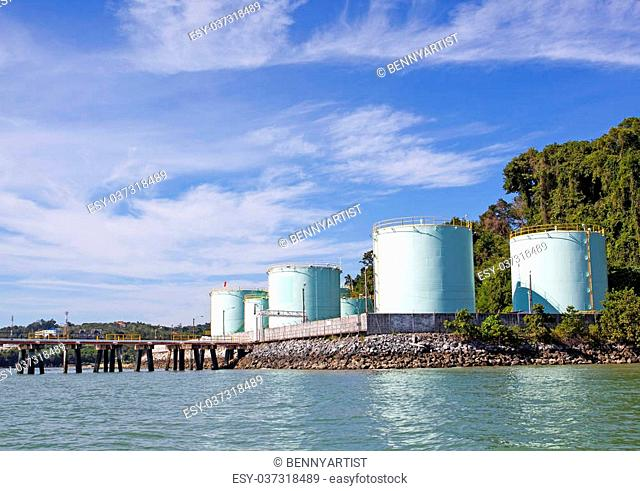 green tanks in tank farm with blue clear sky by the sea