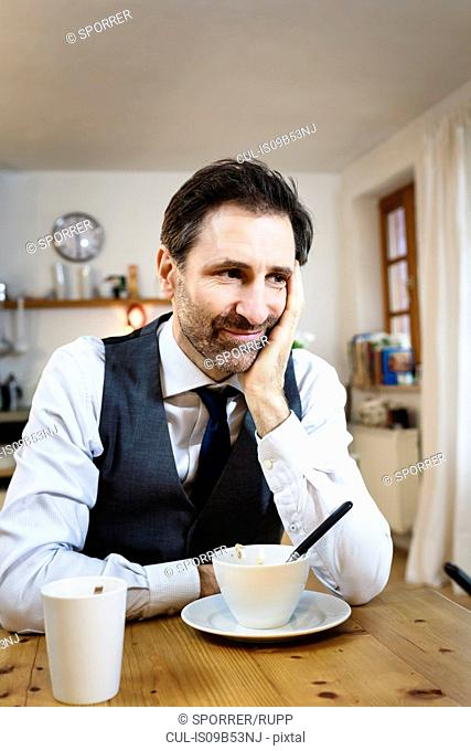 Smiling mature man with chin on hand at breakfast in kitchen