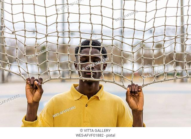 Young black man looking through volleyball net