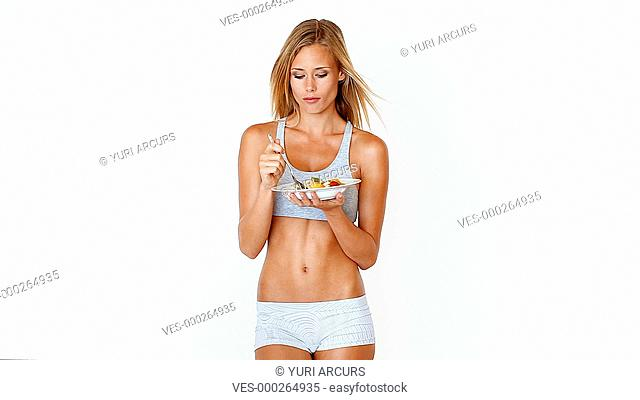 A healthy young woman enjoying a fruit salad and giving you a smile isolated on white