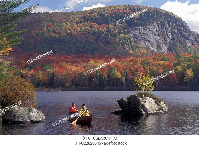 canoeing, autumn, Vermont, VT, Mother and daughter paddle a red canoe on scenic Marshfield Pond surrounded by colorful foliage in the fall