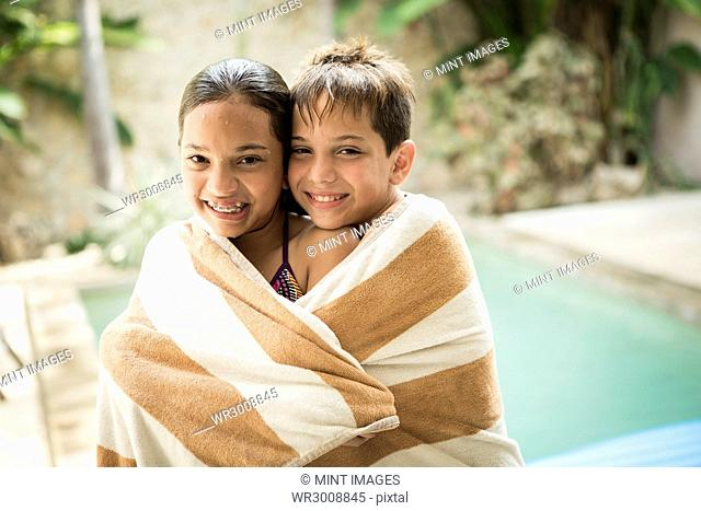 A boy and girl wrapped in a towel and cuddling
