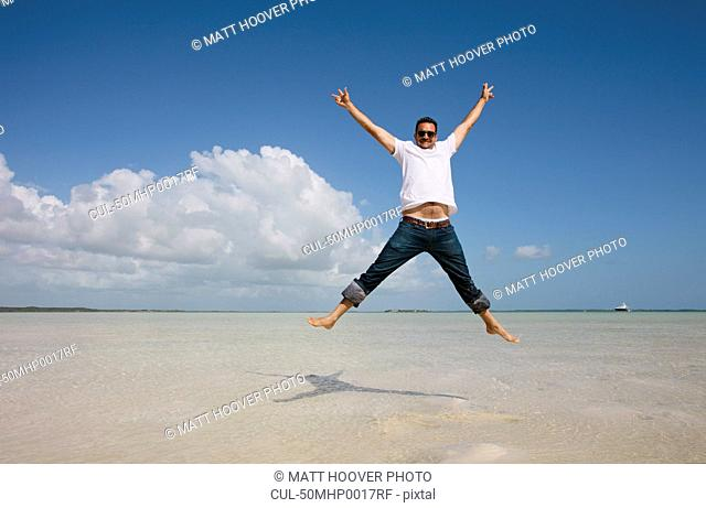 Man jumping in water on tropical beach