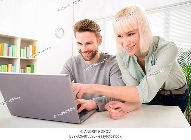 Young Happy Couple Using Laptop On Desk