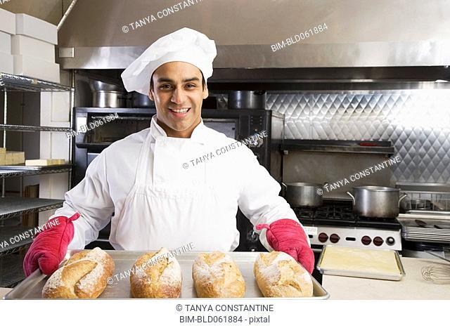 Hispanic male baker holding tray of fresh bread