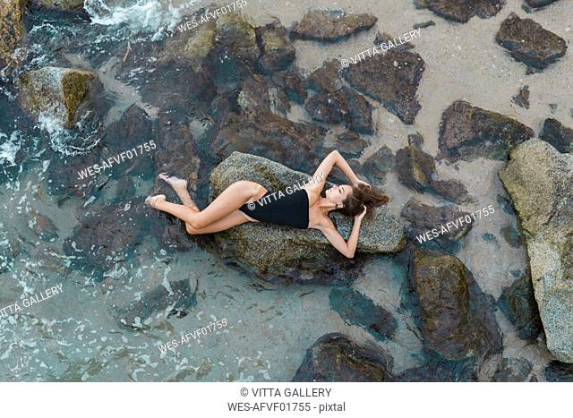 Overhead view of beautiful young woman lying on rock in the sea