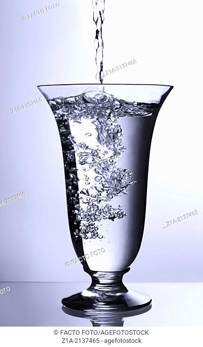 Water pouring into glass container on a gradient blue background