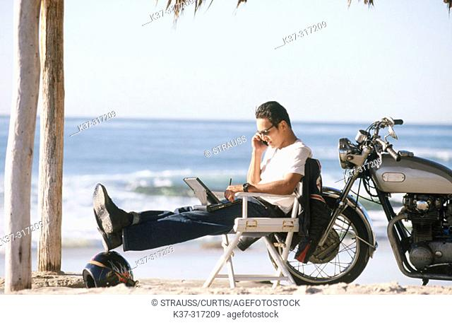 Young Asian Hawaiian man on beach on phone, with motorcycle and laptop computer