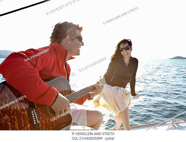 Woman and Man playing guitar on yacht