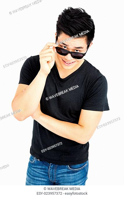 Young man looking over his sunglasses
