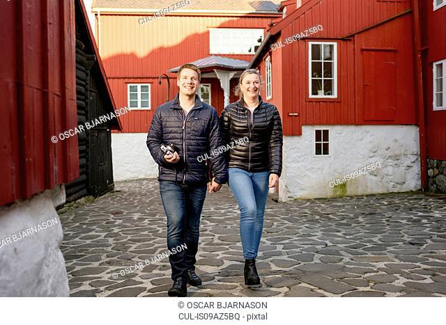Young couple walking through old town, Tinganes, Torshavn, Faroe Islands