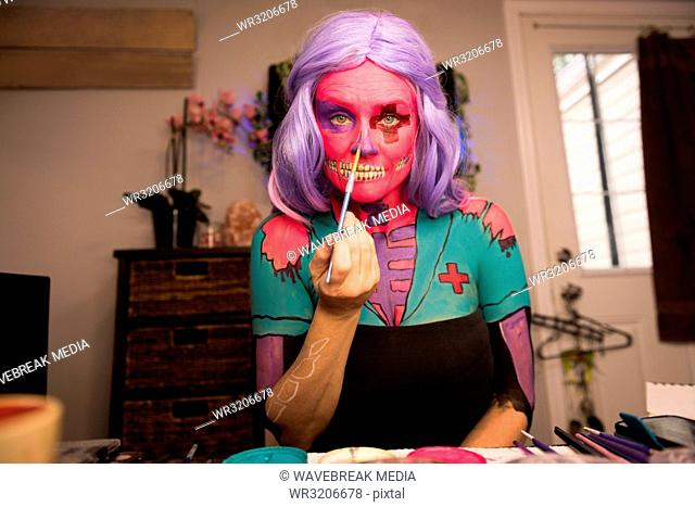 Woman painting her face with brush
