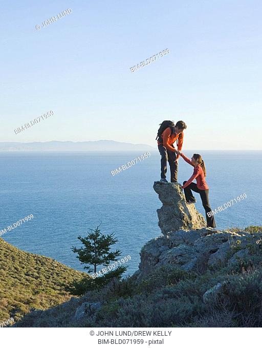 Hispanic couple climbing rock overlooking water