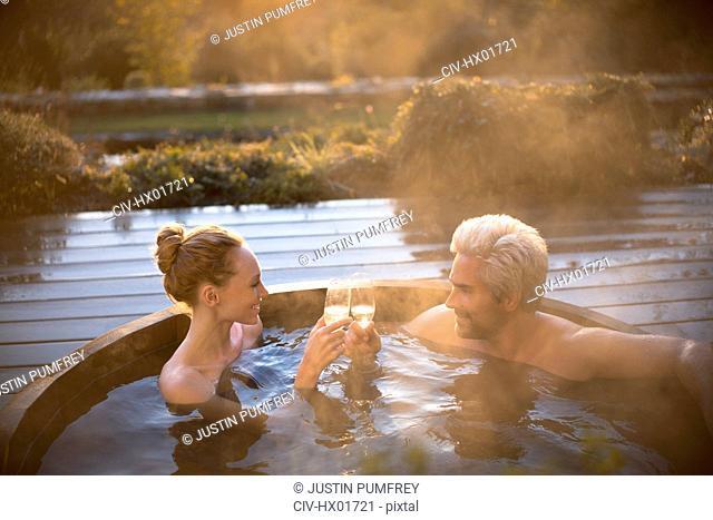 Couple toasting champagne glasses soaking in hot tub on autumn patio
