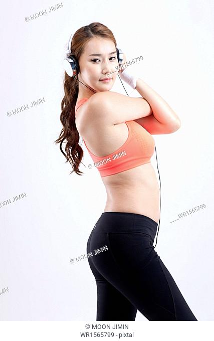 a woman in orange sports top stretching with headset on
