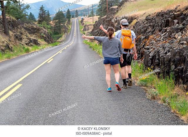 Young couple hiking along road, trying to thumb lift, rear view