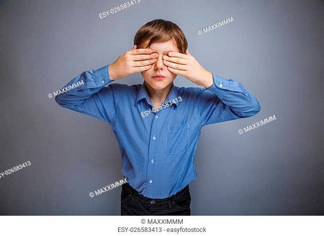 boy in shirt eyes closed hands on a gray background