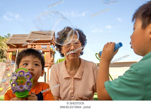 Asian grandmother and grandsons blowing bubbles outdoors