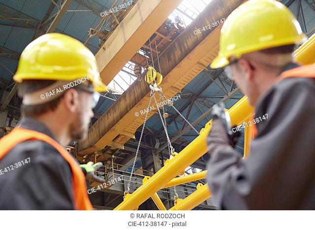Male worker using walkie-talkie to guide hydraulic crane lowering equipment in factory