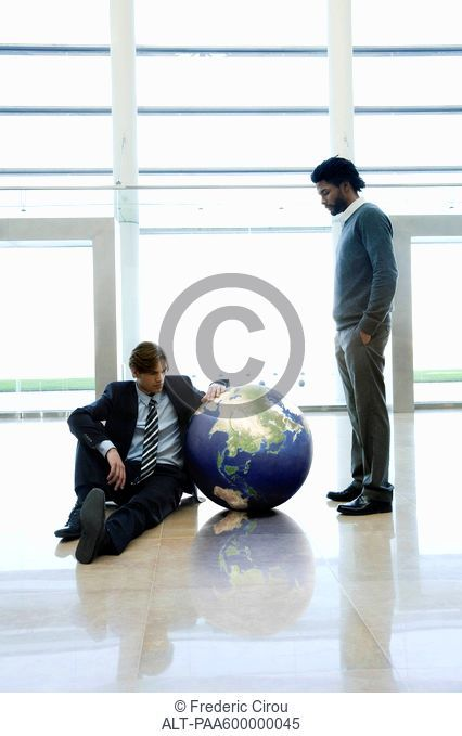 Businessmen contemplating ball in lobby