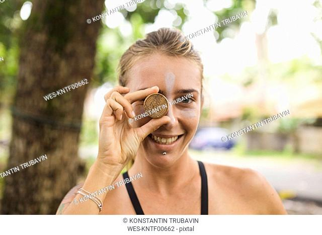 Indonesia, Java, portrait of smiling woman covering her eye with cream pot