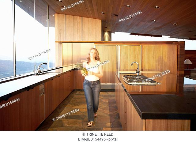 Caucasian woman carrying pineapple in modern kitchen