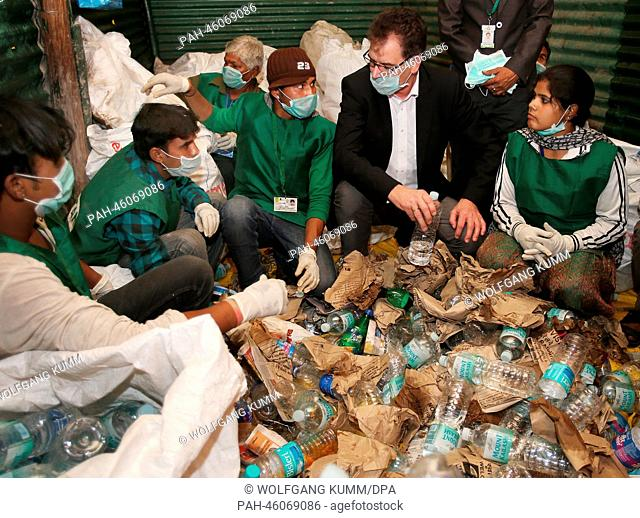 German Development Minister Gerd Mueller visits the Chintan project and watches the sorting of trash in New Dehli, India, 05February 2014