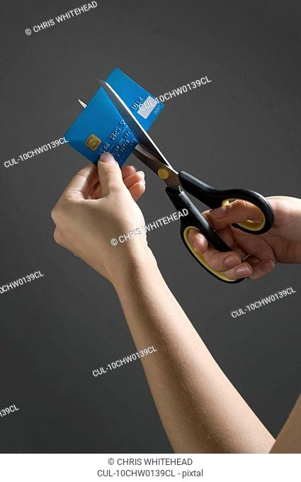 Female hands cutting credit card