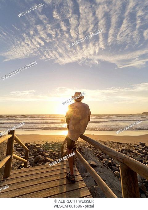 Portugal, Senior man sitting on railing at the beach