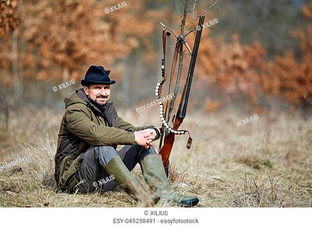 Hunter with double barrel gun in the forest looking for game
