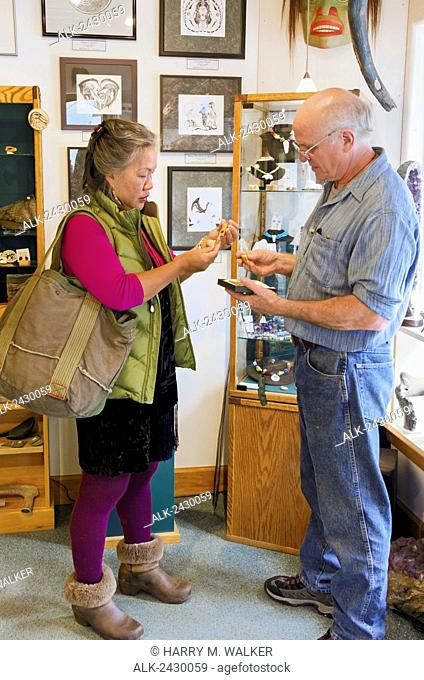 Alaska artist Steve Stegall shows a tourist fossil walrus ivory in his gallery in the historic district of Skagway, Alaska