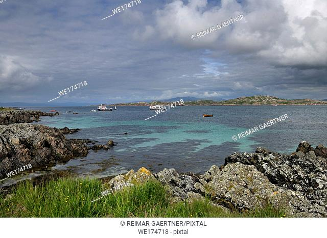 Rocky shore of Isle of Iona looking at Isle of Mull and mountains of Ben More and tour boats in Sound of Iona Inner Hebrides Scotland UK