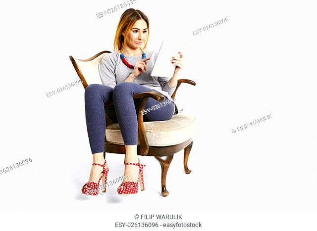 Young woman sitting on an old school chair with tablet reading and watching e-mails