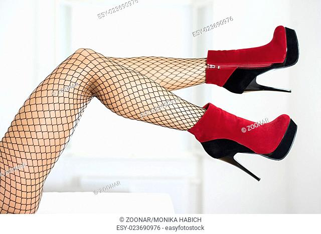 3dce2f1e0d21 Legs of a woman wearing fishnet stockings and red ankle boots