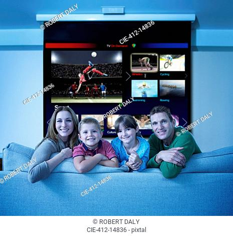 Family watching multi screen television in living room