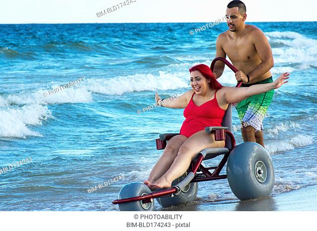 Man pushing paraplegic girlfriend in wheelchair on beach