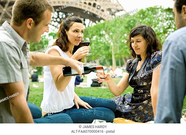 Friends enjoying wine at picnic near Eiffel Tower, Paris, France