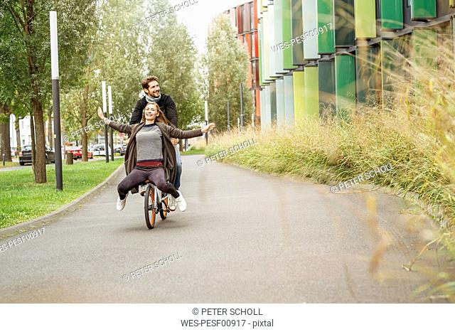 Happy couple riding on one bicycle on a lane