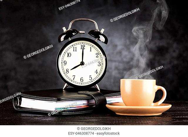Alarm clock and a cup of coffee on dark background