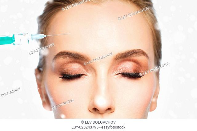 people, cosmetology, plastic surgery, anti-aging and beauty concept - close up of beautiful young woman face and syringe making lifting injection to forehead...