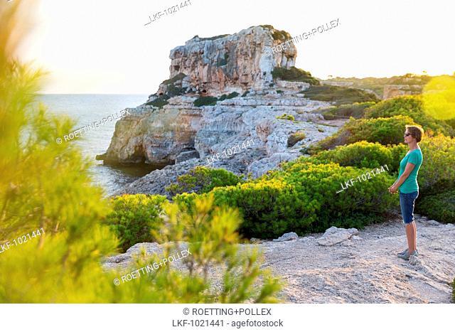 woman looking over the sea, Coastal landscape at Calo des Moro at sunset, Mediterranean Sea, near Santanyi, Majorca, Balearic Islands, Spain, Europe
