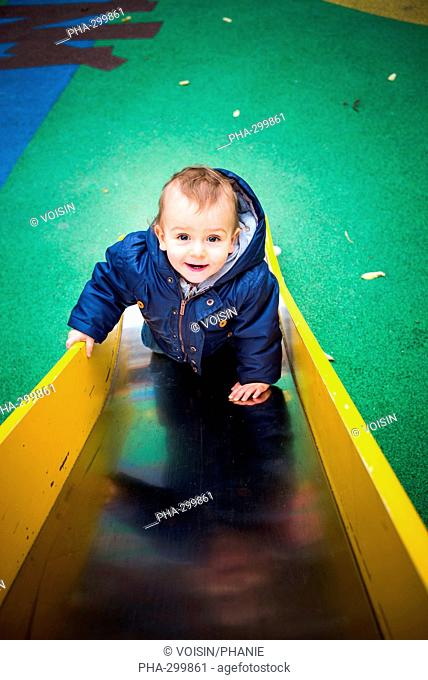18 month-old baby boy on a slide in a playground