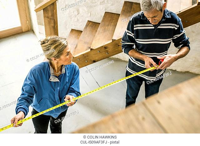 Senior couple doing DIY, using measuring tape