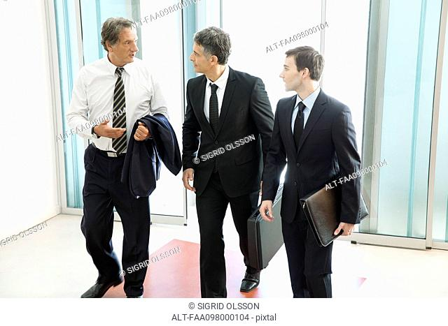 Business associates chatting while entering office building together