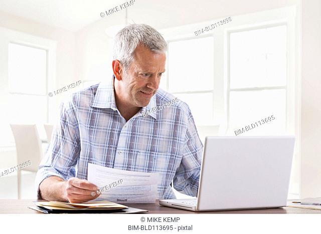Caucasian man paying bills with laptop