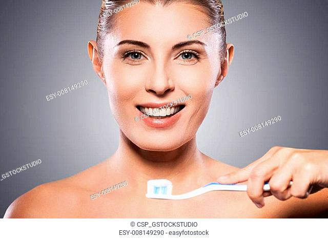 Teeth care. Beautiful mature woman holding toothbrush near her mouth and smiling at camera while standing against grey background